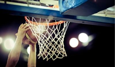 hands dunking basketball in hoop