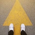 feet on painted road arrow